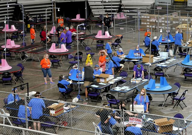 In this 6 May 2021 file photo, Maricopa County ballots cast in the 2020 general election are examined and recounted by contractors working for Florida-based company, Cyber Ninjas at the Veterans Memorial Coliseum in Phoenix. (AP Photo/Matt York, Pool, File)