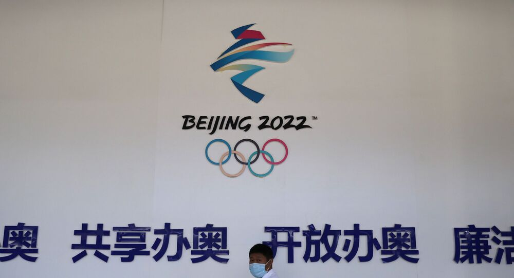 A man walks past a board with a sign of Beijing 2022 Winter Olympic Games at an exhibition hall during an organised media tour to venues of the Games in Zhangjiakou, Hebei province, China July 14, 2021
