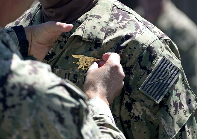 Commander places a special warfare pin on a member of SEAL Qualification Training Class 336 during a graduation ceremony