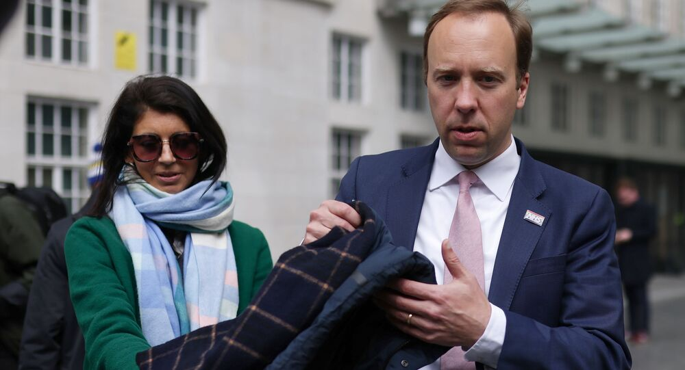 Britain's Health Secretary Matt Hancock hands his coat to his aide Gina Coladangelo (L) before a television interview outside BBC's Broadcasting House in London, Britain, May 16, 2021. Picture taken May 16, 2021