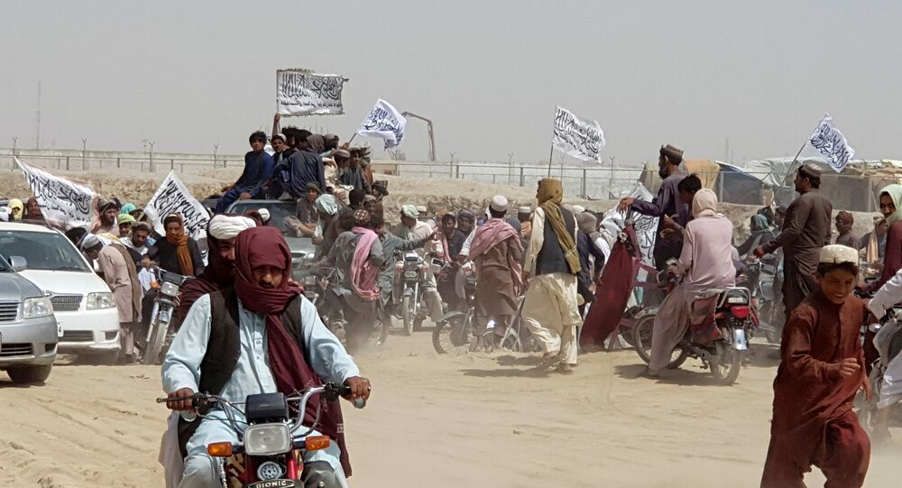People on vehicles, holding Taliban flags, gather near the Friendship Gate crossing point in the Pakistan-Afghanistan border town of Chaman, Pakistan July 14, 2021