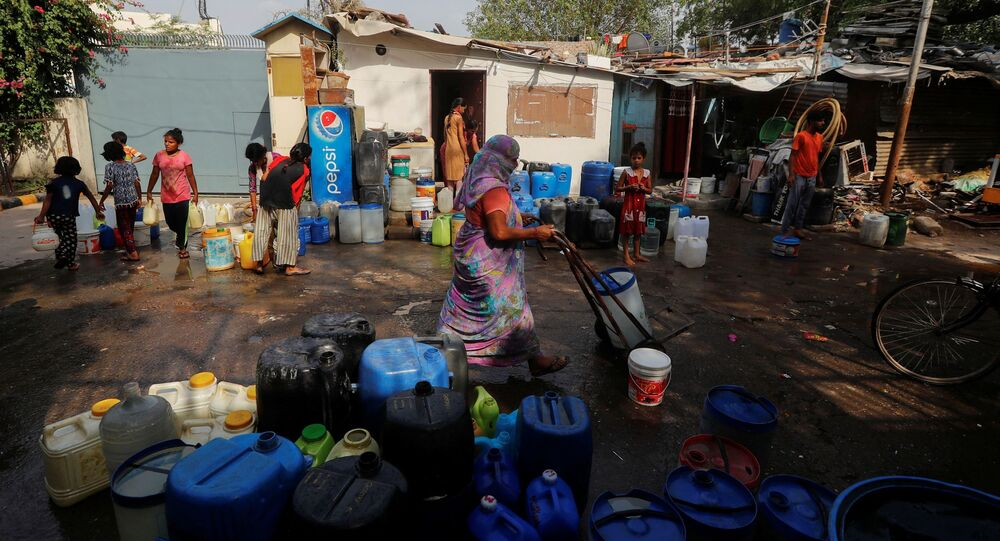 Residents carry containers after filling them with drinking water from a municipal tanker on a hot summer day in New Delhi, India, on 6 July 2021.