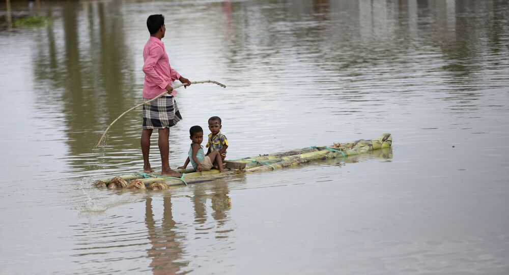 An Indian flood affected man rows a makeshift banana raft with two children in Gagolmari village, Morigaon district, Assam, India, Tuesday, July 14, 2020