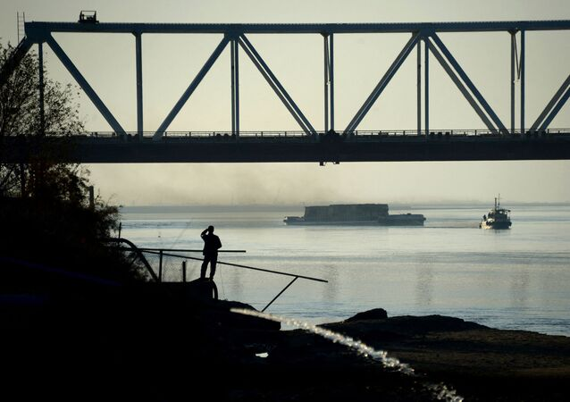 In this photograph taken on November 30, 2015, an Afghan man watches a ship travel along the Amu River on the border of Afghanistan and Uzbekistan, about 75 kms north of Mazar-i-Sharif.
