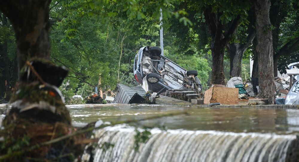 A car stands upside down near floating water in Iversheim, near Bad Muenstereifel, western Germany, on July 16, 2021, following heavy rains and floods. - The death toll from devastating floods in Europe soared to at least 126 on July 16, most in western Germany where emergency responders were frantically searching for missing people.
