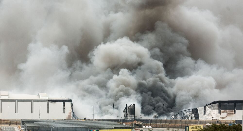 Smoke rises from a Makro building set on fire overnight in Umhlanga, north of Durban, on July 13, 2021 as several shops, businesses and infrastructure are damaged in the city, following four nights of continued violence and looting sparked by the jailing of ex-president Jacob Zuma. - The unrest erupted last on July 9 after Zuma started serving a 15-month term for snubbing a probe into the corruption that stained his nine years in power. In a nationwide address , current President Ramaphosa lashed opportunistic acts of criminality, with groups of people instigating chaos merely as a cover for looting and theft.
