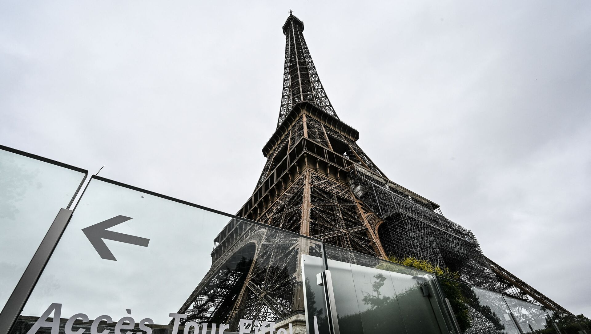 This picture taken on July 16, 2021, in Paris shows the Eiffel Tower and its protective wall. - The Eiffel Tower reopened to visitors on July 16, 2021, after nine months of shutdown caused by the Covid pandemic. Up to 13,000 people per day will be allowed to take the elevators to the top and take in the views over the French capital, down from 25,000 in the pre-Covid era.  - Sputnik International, 1920, 16.07.2021