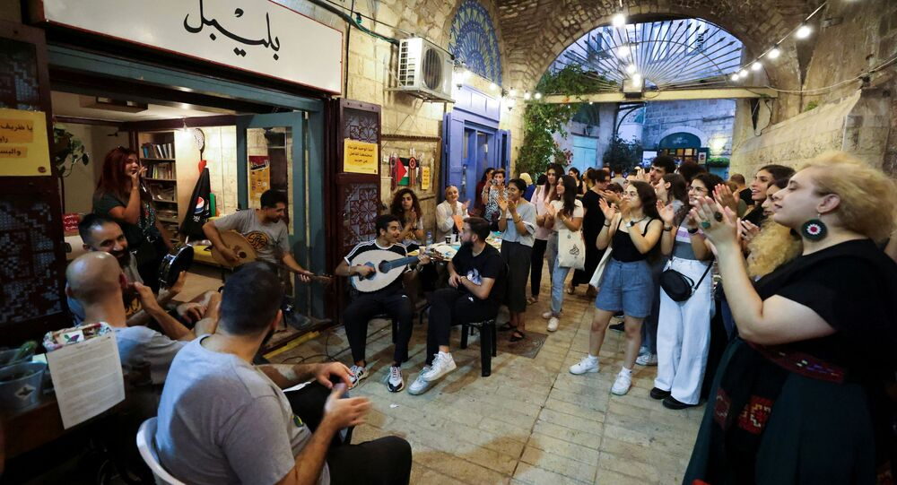 People clap as they watch musicians perform during a happening, part of an initiative launched by young Palestinians aiming to revive Nazareth's old city market, in Nazareth, northern Israel July 11, 2021.