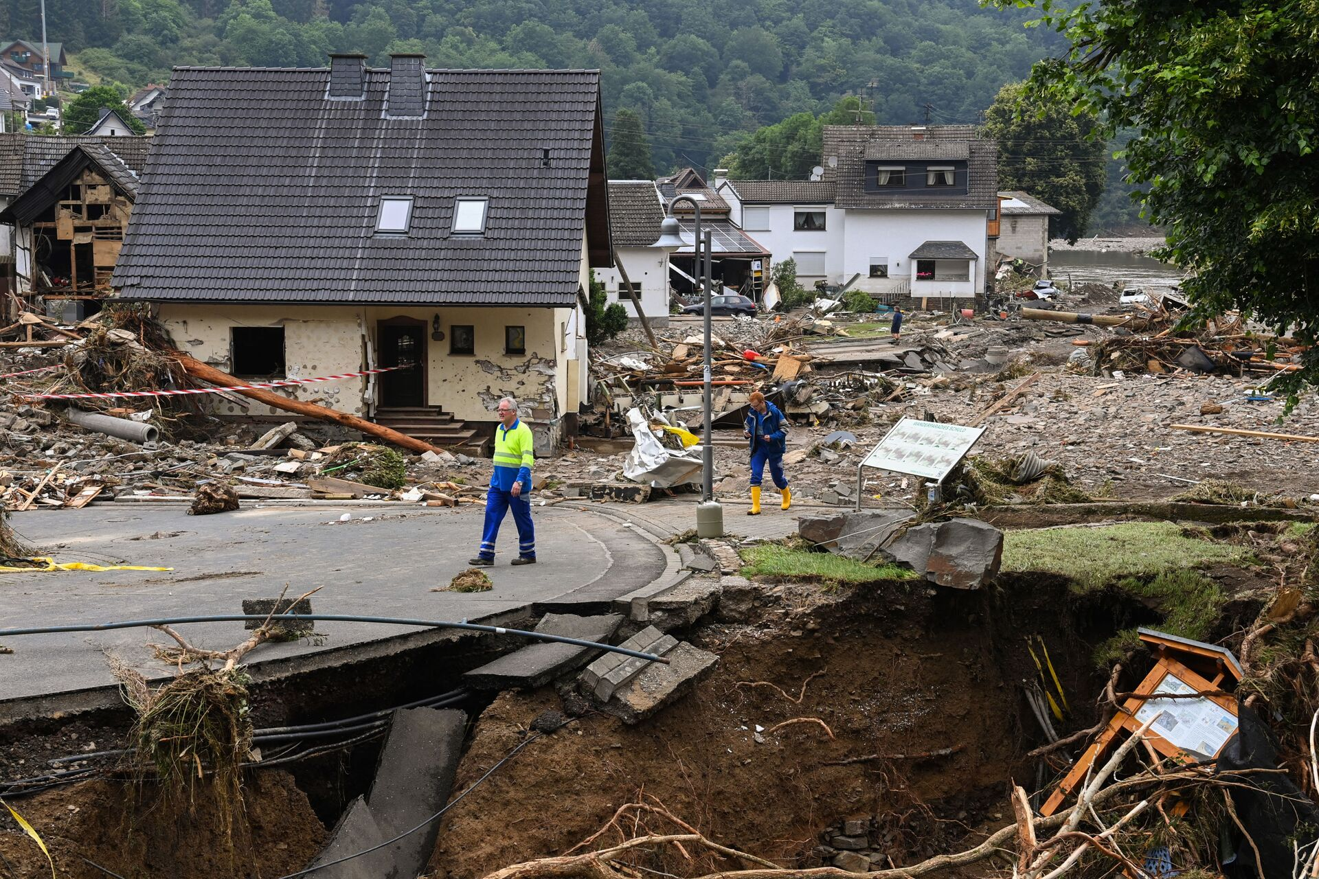 Two men walk on a partially slipped road amid destroyed houses after the floods caused major damage in Schuld near Bad Neuenahr-Ahrweiler, western Germany, on July 16, 2021. - Sputnik International, 1920, 07.09.2021