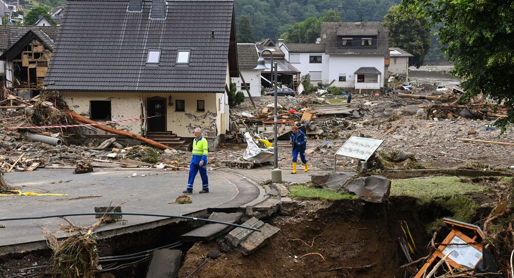 Two men walk on a partially slipped road amid destroyed houses after the floods caused major damage in Schuld near Bad Neuenahr-Ahrweiler, western Germany, on July 16, 2021.