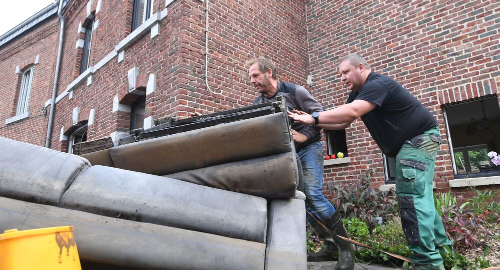 Residents removed damaged furniture from a home following heavy rains and floods in the town of Rochefort on July 17, 2021.