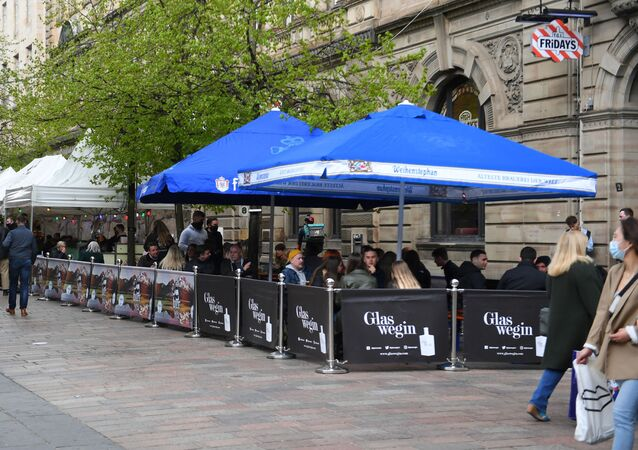 Customers sit at outside tables at a re-opened TGI Fridays restaurant in Glasgow on April 26, 2021 following the relaxing of some Covid-19 restrictions in Scotland, after the third national lockdown.