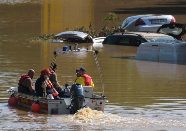 A rescue boat patrols next to submerged vehicles on the federal highway B265 in Erftstadt, western Germany, on 17 July 2021.
