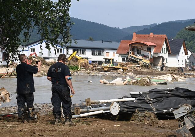 A worker (L) takes a picture of a destroyed area in Insul near Bad Neuenahr-Ahrweiler, western Germany, on July 17, 2021. - Devastating floods in Germany and other parts of western Europe have been described as a catastrophe, a war zone and unprecedented, with more than 150 people dead and the toll still climbing on July 17, 2021