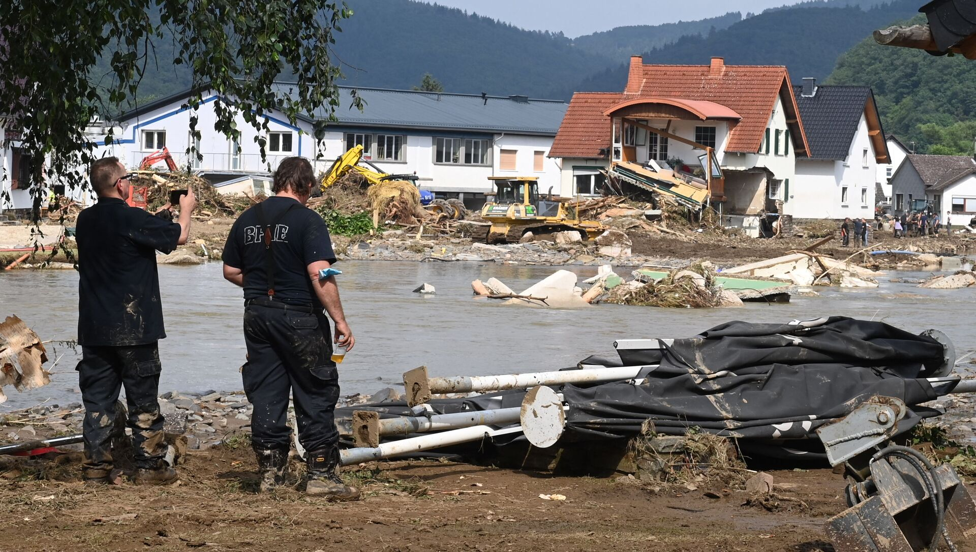 A worker (L) takes a picture of a destroyed area in Insul near Bad Neuenahr-Ahrweiler, western Germany, on July 17, 2021. - Devastating floods in Germany and other parts of western Europe have been described as a catastrophe, a war zone and unprecedented, with more than 150 people dead and the toll still climbing on July 17, 2021 - Sputnik International, 1920, 28.07.2021