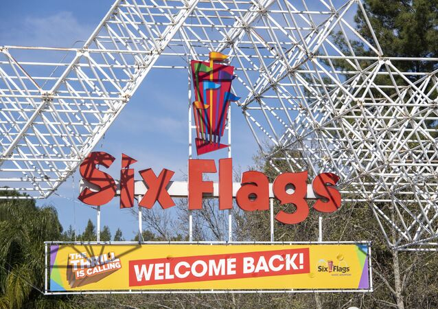 A sign at the entrance of the theme park Six Flags Magic Mountain welcomes the public back on the day of the park's re-opening, April 1, 2021, in Valencia, California. - Six Flags Magic Mountain is the first theme park to re-open in Los Angeles County after closures amid the coronavirus pandemic.