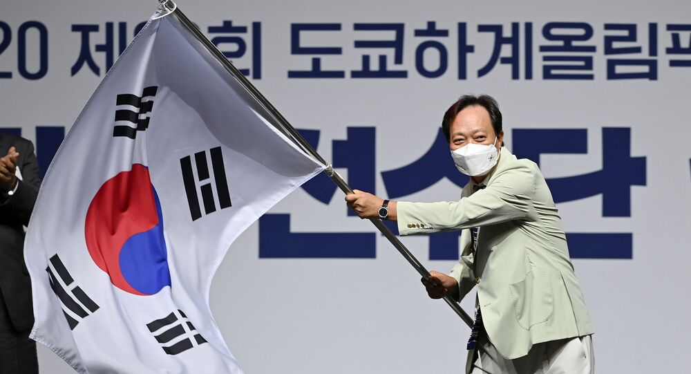 Head of South Korea's delegation to Tokyo 2020 Olympic Games, Jang In-hwa, waves the national flag during an inaugural ceremony ahead of the team's departure for Japan, in Seoul, South Korea, 8 July 2021