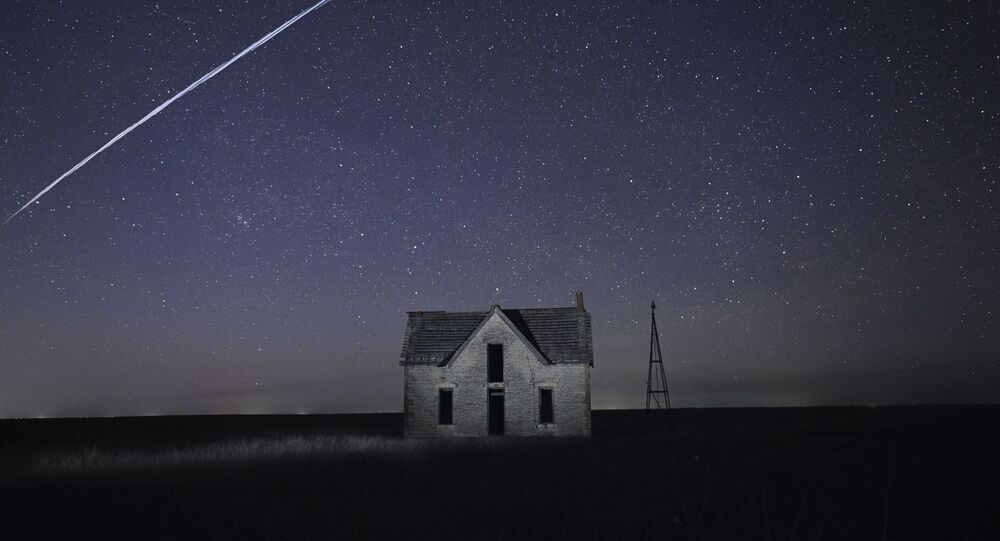 File-In this photo taken May 6, 2021, with a long exposure, a string of SpaceX StarLink satellites passes over an old stone house near Florence, Kan