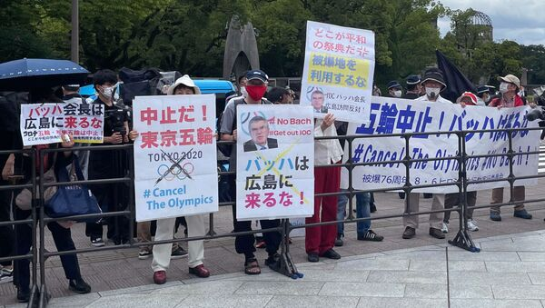 Protesters hold banners and placards including one (C) that reads Bach, Do not come to Hiroshima! ahead of the arrival of International Olympic Committee President Thomas Bach to the Hiroshima Memorial Cenotaph, in Hiroshima on July 16, 2021.  - Sputnik International