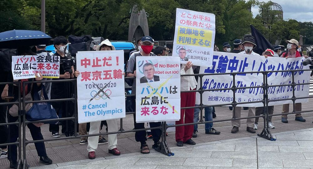 Protesters hold banners and placards including one (C) that reads Bach, Do not come to Hiroshima! ahead of the arrival of International Olympic Committee President Thomas Bach to the Hiroshima Memorial Cenotaph, in Hiroshima on July 16, 2021.