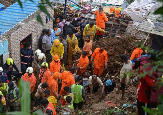 National Disaster Response Force (NDRF) and other rescue team personnel inspect the site of the landslide in a slum area where 18 people were killed after several homes were crushed by a collapsed wall and a landslide triggered by heavy monsoon rains in Mumbai on 18 July 2021.