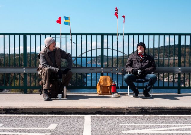 Pontus Berglund (L) sits on the Swedish side while his brother Ola sits on the Norwegian side of the old bridge of Svinesund with the respective country flags and the new Svinesund Bridge in the background, in Svinesund, Norway  and Sweden, on May 1, 2021