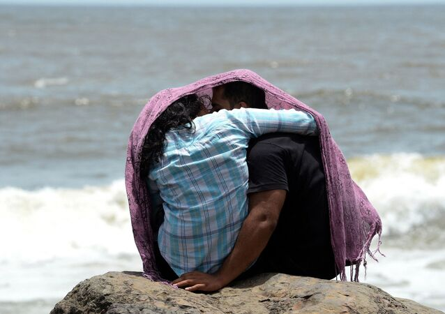 A young couple sit together on a rocky outcrop off the Arabian sea in Mumbai on July 3, 2015