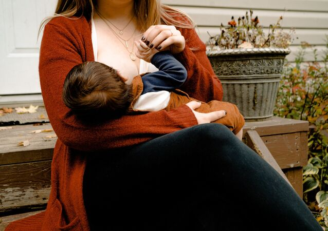 Photo Of Woman Breastfeeding Her Child