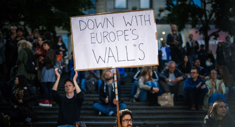 A man holds a sign as he takes part in a demonstration in solidarity with migrants seeking asylum in Europe after fleeing their home countries in Stockholm on September 12, 2015.