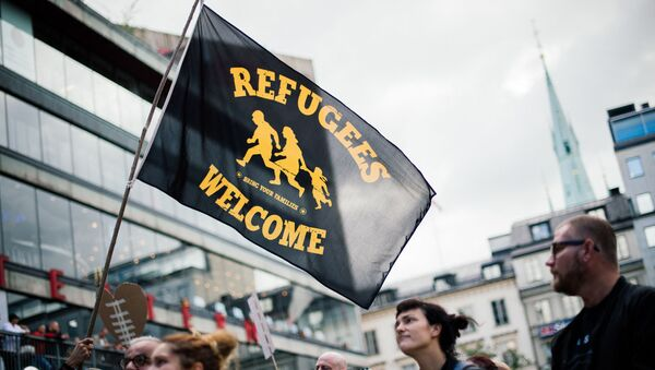 People take part in a demonstration in solidarity with migrants seeking asylum in Europe after fleeing their home countries in Stockholm on September 12, 2015. - Sputnik International