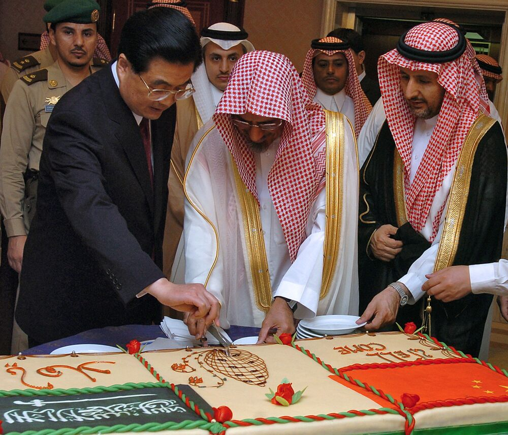 The chairman of the Saudi Shura consultative council, Sheikh Saleh bin Humaid (2nd L) and Chinese President Hu Jintao (L) cut a cake after Jintao's speech at the Shura Council in Riyadh on 23 April 2006.