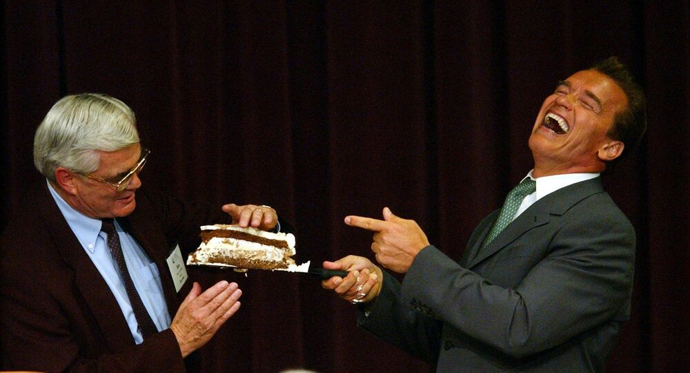 California Governor Arnold Schwarzenegger, right, shares a slice of birthday cake with Riverside Mayor and League of California Cities president Ron Loveridge after speaking at the mayors and council members forum in Monterey, California on Thursday, 29 July 2004.