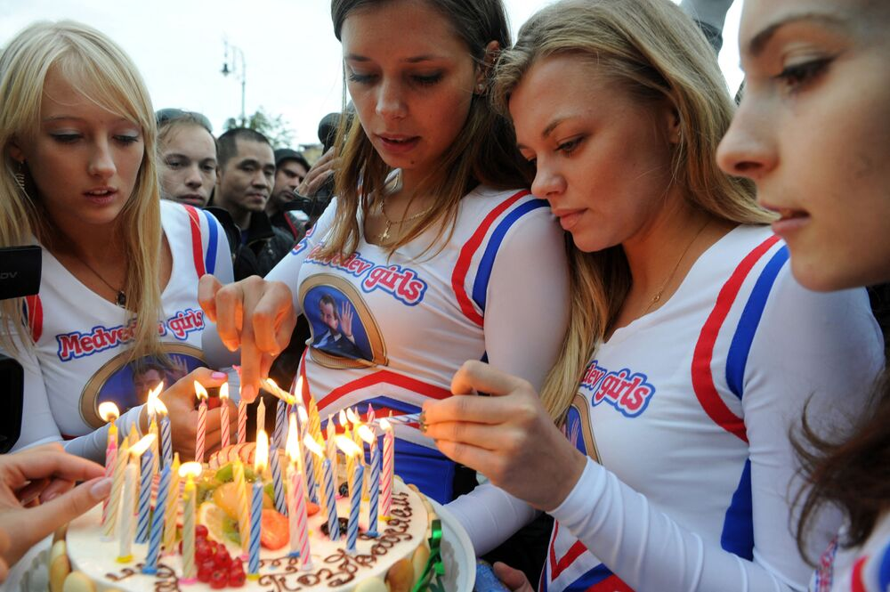 Medvedev Girls, members of an internet community supporting Russia's President Dmitry Medvedev, hold a birthday cake during their staged action marking Medvedev's 46th birthday  in Moscow,  on 14 September 2011.