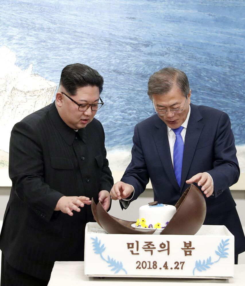 North Korean leader Kim Jong Un, left, and South Korean President Moon Jae-in, right, marvel at a chocolate dome cake during a banquet at the border village of Panmunjom in the Demilitarised Zone, South Korea, on Friday, 27 April 2018.