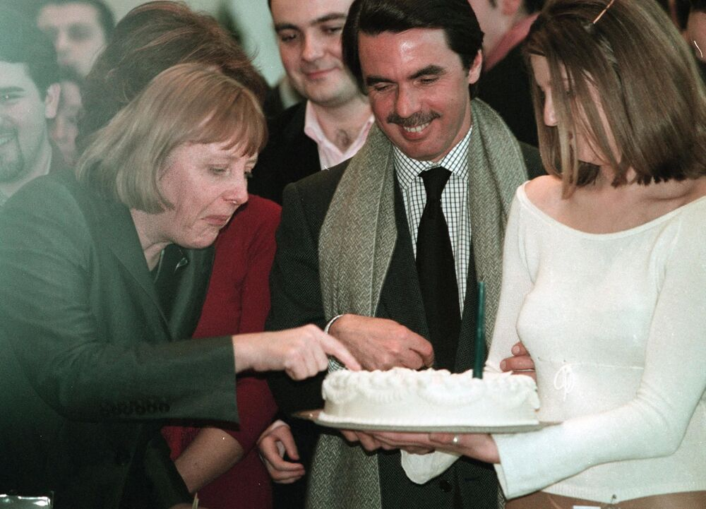 President of German CDU party, Angela Merkel (L), tastes the birthday cake of Spanish Prime minister Jose Maria Aznar (C) during the meeting Europe, passion for freedom organised by youths of the Spanish ruling Popular Party, in Bilbao, Spain.