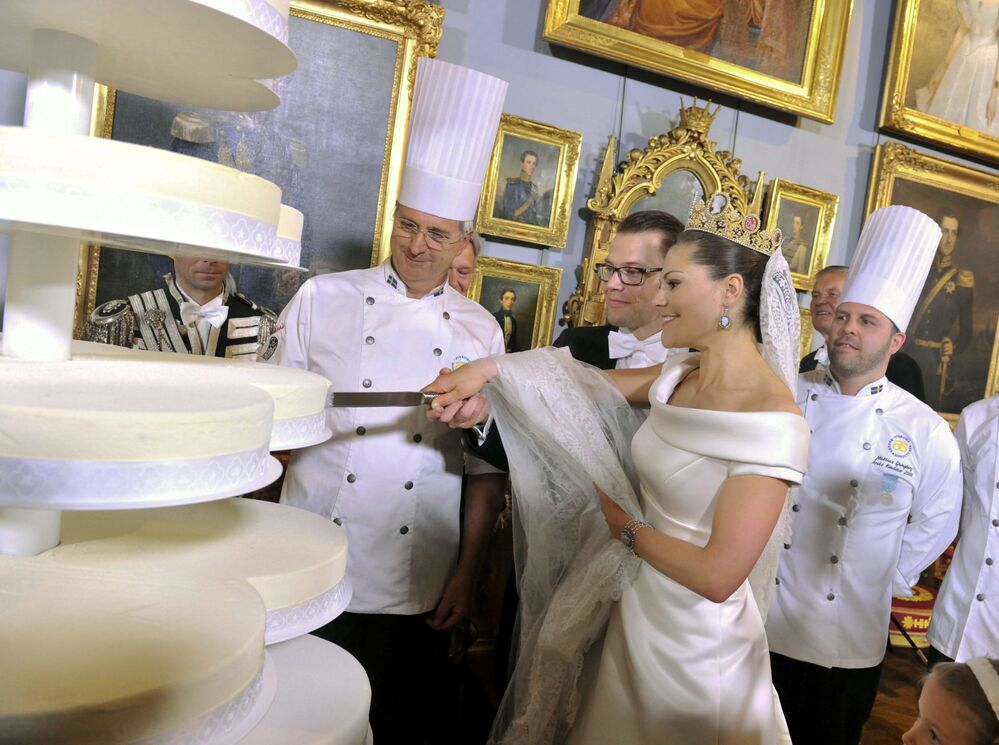 Swedish Crown Princess Victoria (front R) and Prince Daniel Westling (front L), the Duke of Vastergotland, cut their wedding cake during celebrations for their marriage at the Royal Palace in central Stockholm, Sweden on 19 June, 2010.