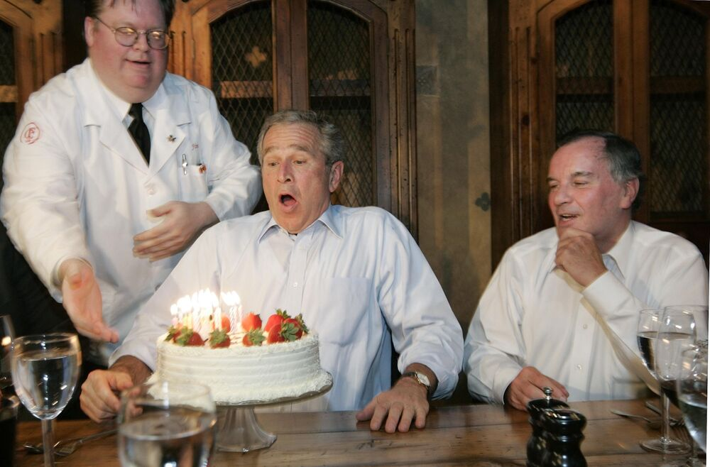 Former President George W Bush, left, prepares to blows out the candles on his birthday cake as he celebrates with Richard M. Daley, right, Mayor of Chicago, at the Chicago Firehouse restaurant, on 6 July 2006, in Chicago, US.