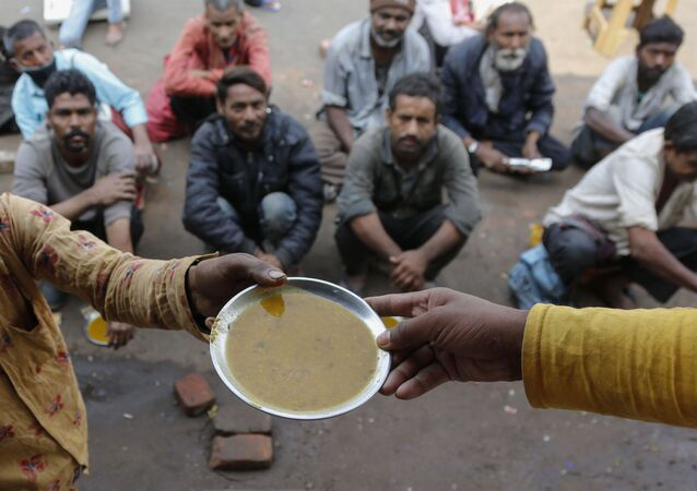 People wait for free food outside an eatery in Ahmedabad, India, Wednesday, Jan. 20, 2021