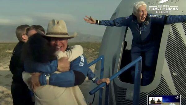 Billionaire businessman Jeff Bezos and pioneering female aviator Wally Funk emerge from their capsule after their flight aboard Blue Origin's New Shepard rocket on the world's first unpiloted suborbital flight near Van Horn, Texas, U.S., July 20, 2021 in a still image from video - Sputnik International