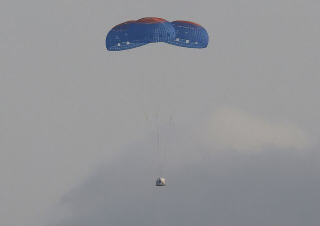 The capsule carrying billionaire businessman Jeff Bezos and three crew members returns by parachute after their flight aboard Blue Origin's New Shepard rocket near Van Horn, Texas , US, on 20 July 2021.