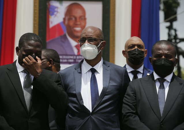 Haiti's designated Prime Minister Ariel Henry, center, and interim Prime Minister Claude Joseph, right, pose for a group photo with other authorities in front of a portrait of late Haitian President Jovenel Moise at at the National Pantheon Museum during a memorial service in Port-au-Prince, Haiti, Tuesday, July 20, 2021.