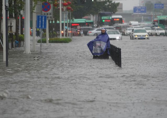 A resident wearing a rain cover stands on a flooded road in Zhengzhou, Henan province, China July 20, 2021.