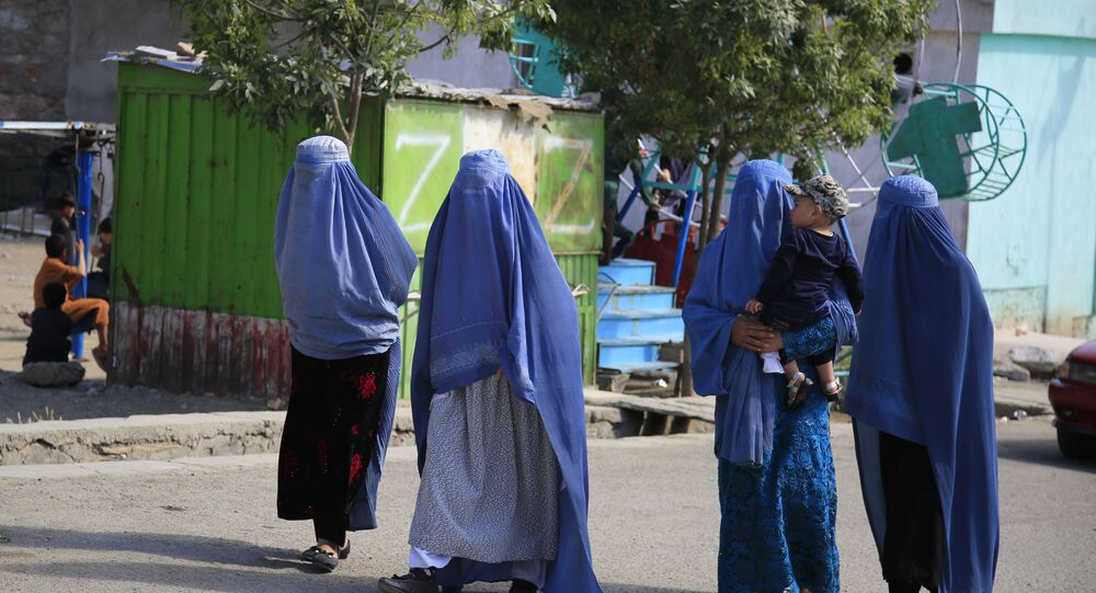 Afghan women walk on the road during the first day of Eid al-Fitr in Kabul, Afghanistan, Thursday, May 13, 2021