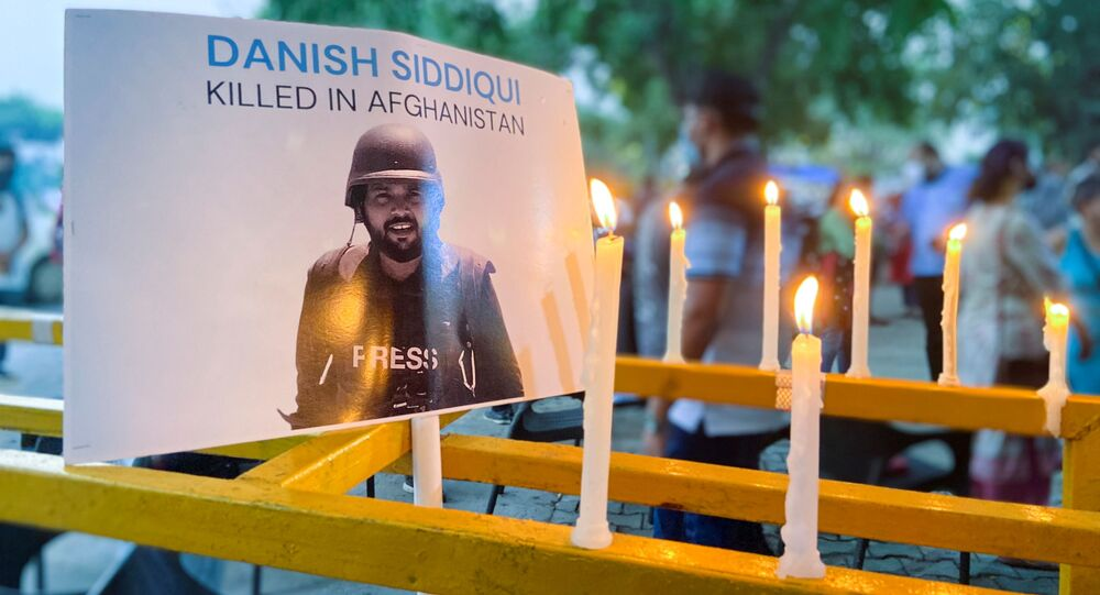 Candles are seen lit next to a photograph of Reuters journalist Danish Siddiqui, after he was killed while covering a clash between Afghan security forces and Taliban fighters near a border crossing with Pakistan, outside the Press Club during a vigil in New Delhi, India, July 17, 2021.