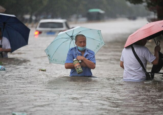 Residents wade through floodwaters on a flooded road amid heavy rainfall in Zhengzhou, Henan province, China July 20, 2021. Picture taken July 20, 2021.