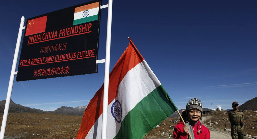 An Indian girl poses for photographs with an Indian flag at the Indo-China border at the Bum La Pass at an altitude of 15,700 feet (4,700 meters) above sea level in Arunachal Pradesh, India on Sunday 21 October 2012.