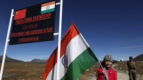 An Indian girl poses for photographs with an Indian flag at the Indo China border in Bumla at an altitude of 15,700 feet (4,700 meters) above sea level in Arunachal Pradesh, India, Sunday, Oct. 21, 2012 - Sputnik International