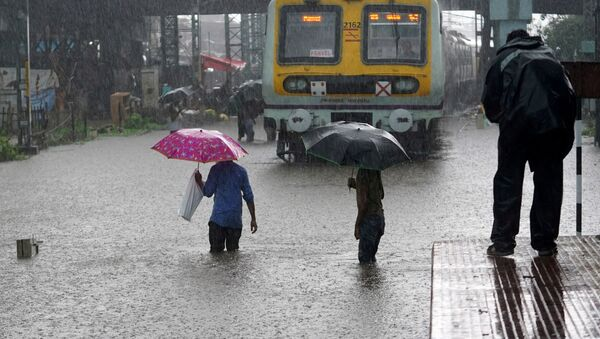 People cross inundated railway tracks next to a parked passenger train during heavy monsoon rains in Mumbai, India, June 9, 2021 - Sputnik International