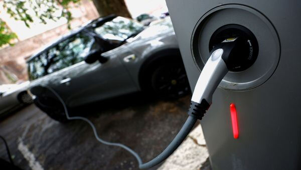 An electric car is seen plugged in at a charging point for electric vehicles (File) - Sputnik International
