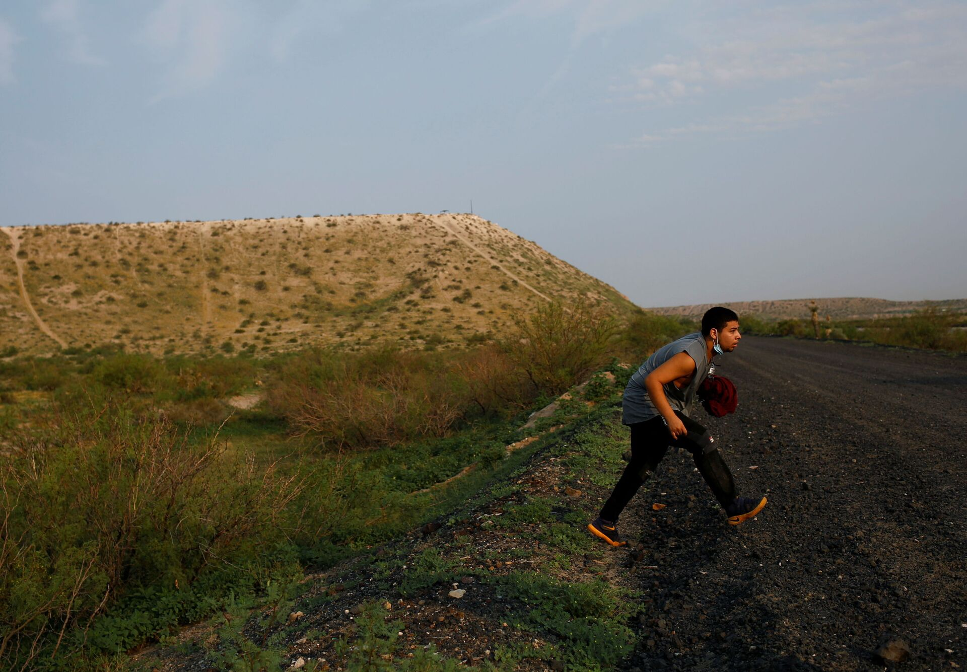 A migrant from Guatemala runs to hide from U.S. Border Patrol after crossing into the United States from Mexico, in Sunland Park, New Mexico, U.S., July 22, 2021 - Sputnik International, 1920, 07.09.2021